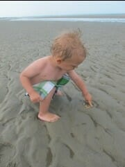 A toddler playing on the beach