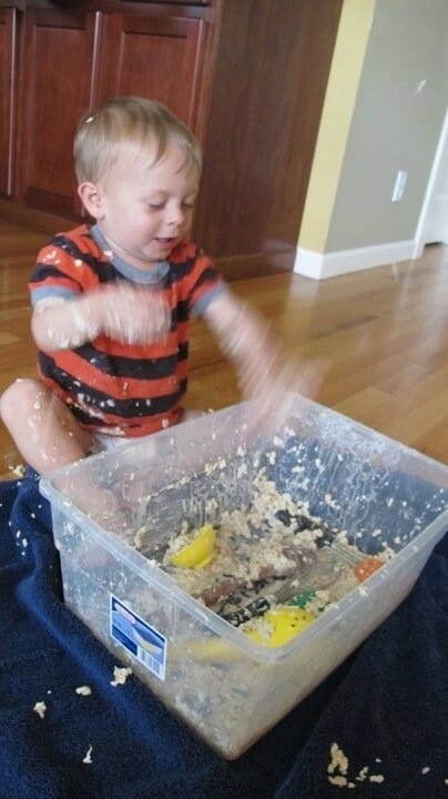 Boy playing in a messy sensory tub