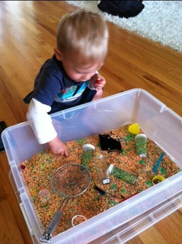 Young boy playing in a sensory tub