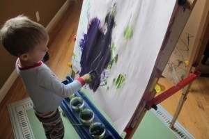 toddler painting at easel