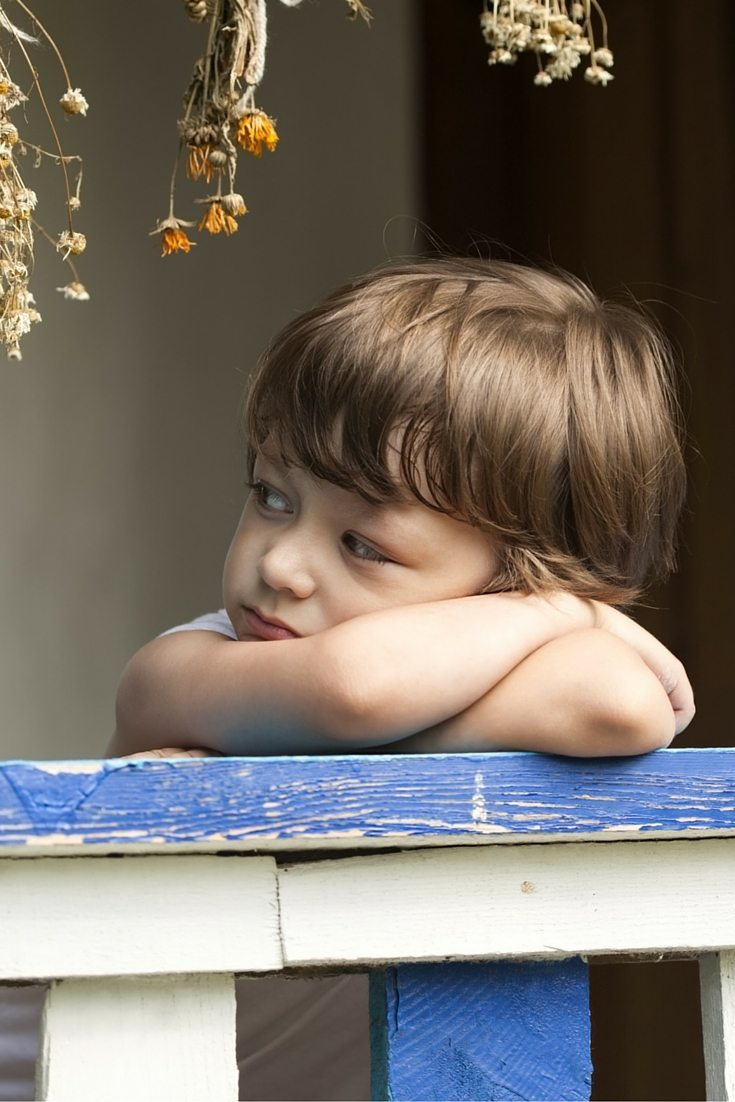 a young boy leaning on a fence