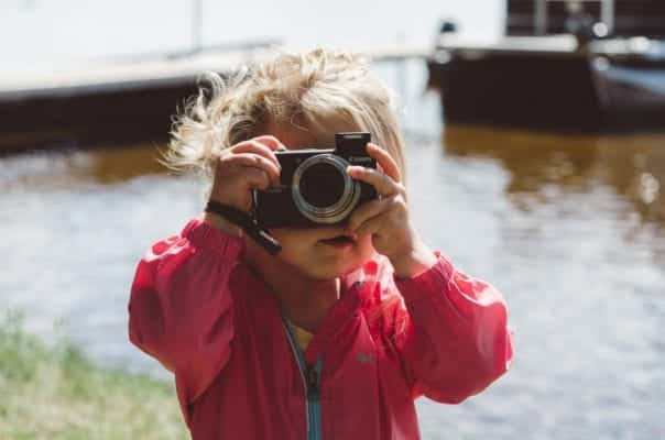 A young girl taking a photograph.