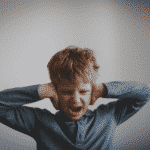 anxious child covering his ears
