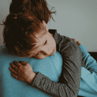 anxious child getting hug from mother